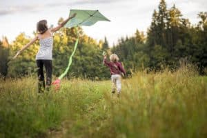 Young mother helping her child to fly a kite